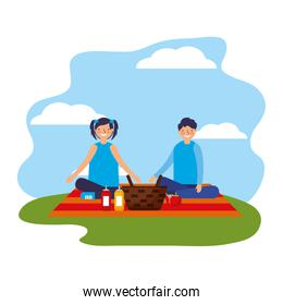 couple sitting on blanket with picnic basket