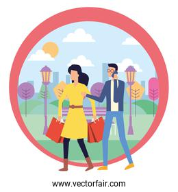 man using smartphone and woman with shopping bag in the park