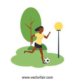 Woman playing with soccer ball at park