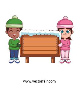 Boy and girl with winter clothes and wooden sign