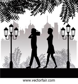 silhouette man radio and woman walking park twon background
