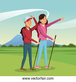 young couple hiking with backpack walking sticks landscape