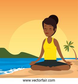 afro woman practicing yoga on the beach