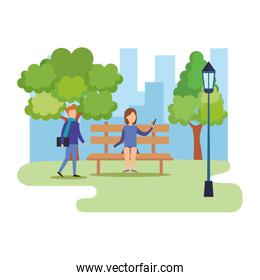young couple with smartphone on park chair