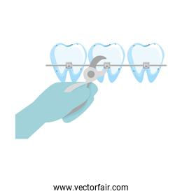 human teeth with hand orthodontist and pliers