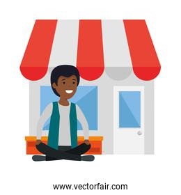 young black man in lotus position with store building