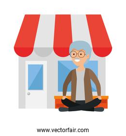 old man in lotus position with store building