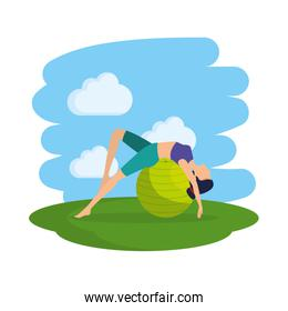 woman practicing yoga position with balloon in the field