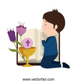 little boy kneeling with book and chalice first communion