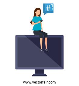 woman using smartphone seated in desktop with speech bubble