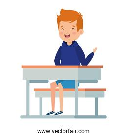 happy little student boy seated in school desk