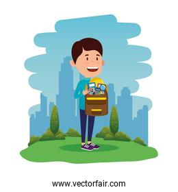 happy student boy with schoolbag in the field