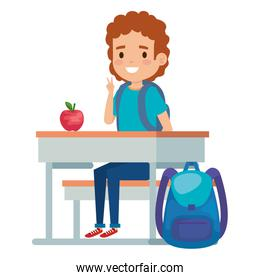 student boy seated in school desk with apple and bag