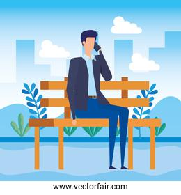 elegant businessman calling with smartphone seated in the park chair