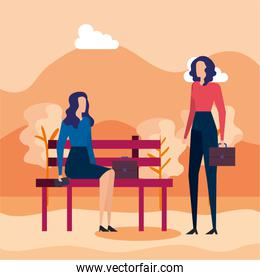 elegant businesswomen seated in the park chair