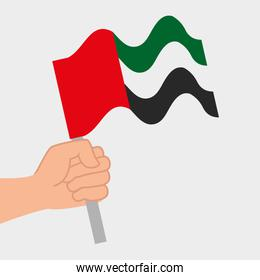 hand with United Arab Emirates flag waving in pole over gray
