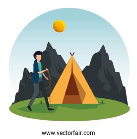 man walking with stick and camp with mountains and sun
