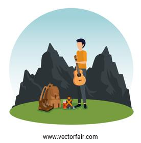man with guitar and backpack in the nature mountains