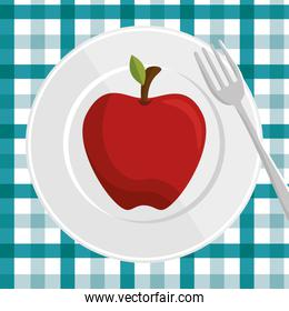 fresh apple over plate and fork with checkered tablecloth