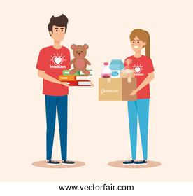 boy and girl volunteers with box and teddy with books