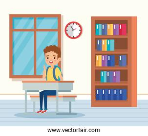boy child in the classroom with desk and window