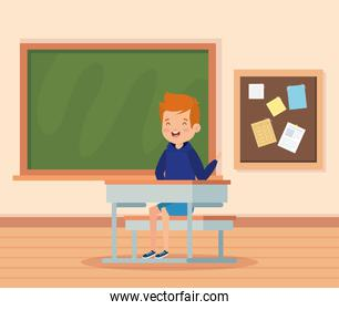 boy child in the classroom with desk and blackboard
