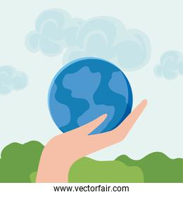 hand with planet earth in landscape