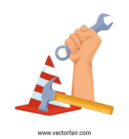 hand holding a wrench and safety cone with a hammer