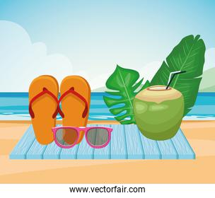 sandals, coconut drink and tropical leaves at the beach