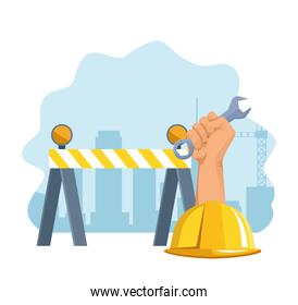 road barrier with safety helmet and hand holding a wrench