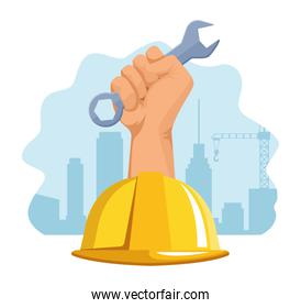 safety helmet and hand holding a wrench tool