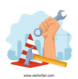 traffic cone and hand holding a wrench and hammer