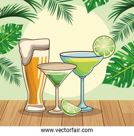 beer glass and tropical cocktails over tropical leaves and retro style background