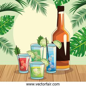 whisky bottle and tropical cocktails over tropical leaves and retro style background
