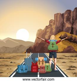 beautiful western landscape with travel bags and traveler man with his arms wide open