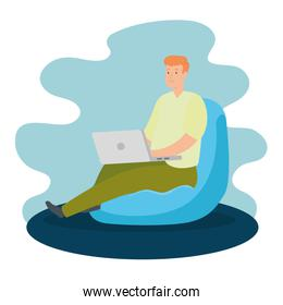 man working at home with laptop sitting in pouf