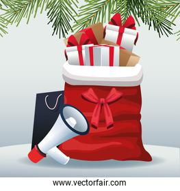 Megaphone and Christmas bag with gift boxes over gray background