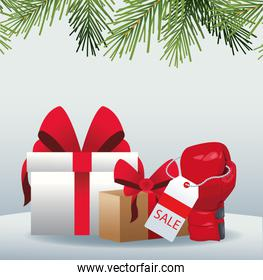 Gift boxes and boxing glove with sale tag over gray background