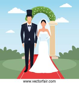 Groom and bride standing over floral arch and landscape background