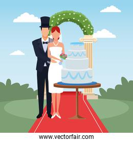 just married couple standing with wedding cake and floral arch around