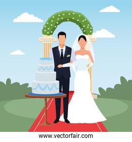 Wedding scenery with Just married couple with wedding cake and floral arch