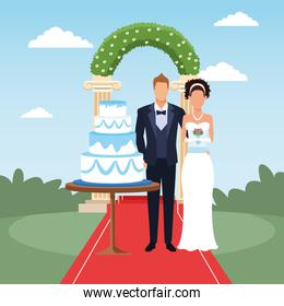 just married couple standing with wedding cake and floral arch around, colorful design