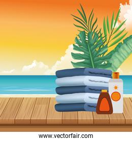 summer time in beach vacations folded towels sunblock bronzer sea leaves