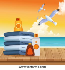 summer time in beach vacations folded towels sunblock bronzer bottles seagulls sea