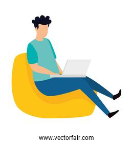 man sitting in pouf with laptop
