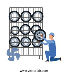 car mechanic holding a tire of tires rack