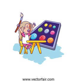 little student girl sitting in school desk with palette colors