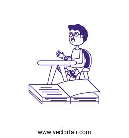 cute little student boy in desk with book open