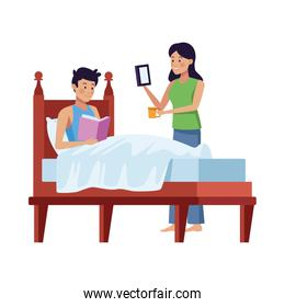 couple using smartphone and reading book in bedroom