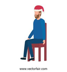 young man with christmas hat seated in chair